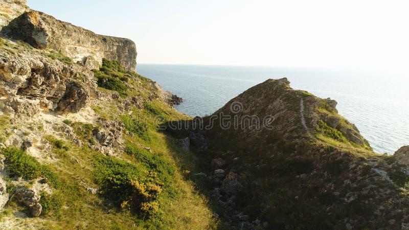 Pokojowy błękitny morze i świeża zielona trawa skalisty skłon przy wybrzeże strzałem Magiczna ścieżka niekończący się morze z jas zdjęcia royalty free