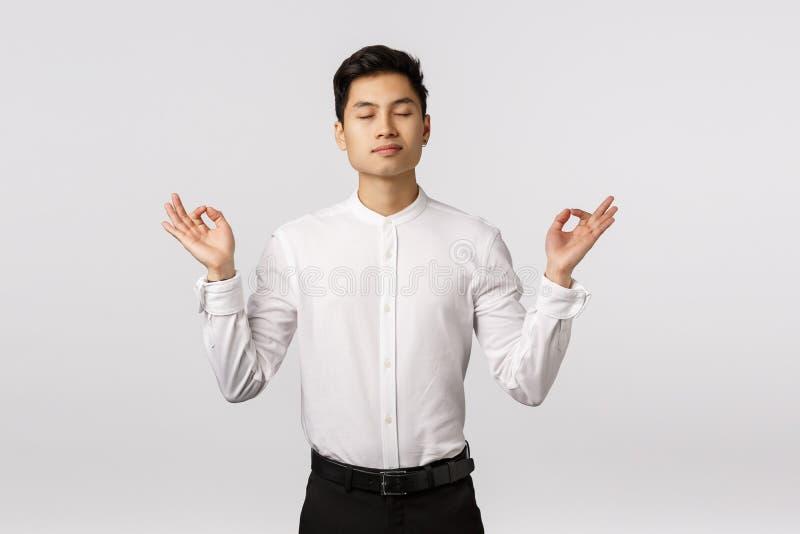 Pokojowy i zdecydowany atrakcyjny azjatycki biznesmen, uspokój się, uwolnij stres, zamknij oczy i medytując w biurze obrazy royalty free