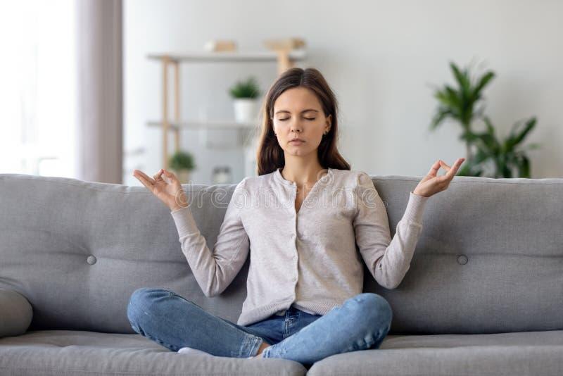 Pokojowy młodej kobiety obsiadanie w lotosowej pozie na kanapie, medytuje w domu obraz stock