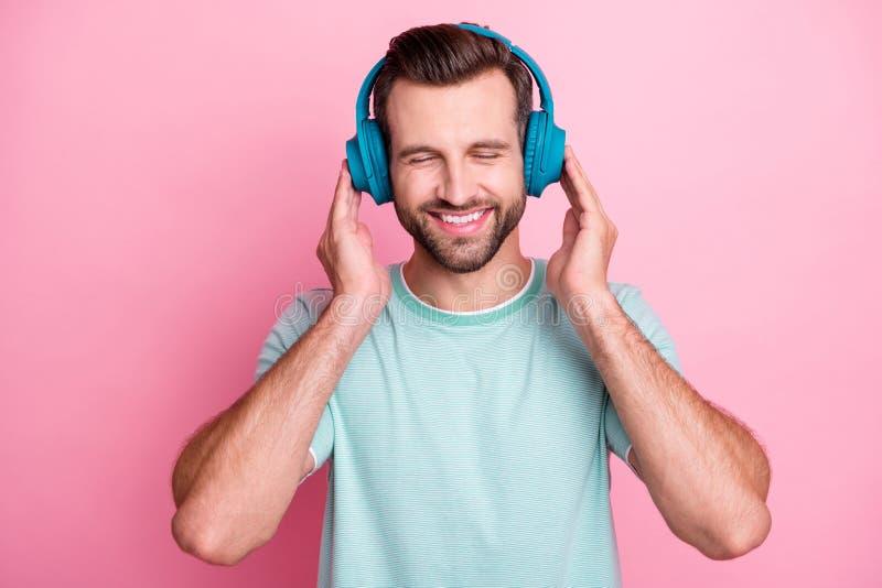 Pokojowy, pozytywny nowoczesny człowiek ma niebieski bezprzewodowy zestaw słuchawkowy słuchaj muzyki ciesz się melodią bliskie oc fotografia stock
