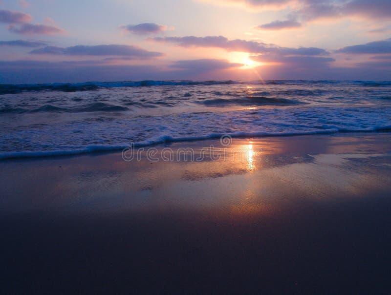 Pokojowy widok chmurny zmierzch na piaskowatej plaży z pięknymi odbiciami na mokrym piasku obraz royalty free