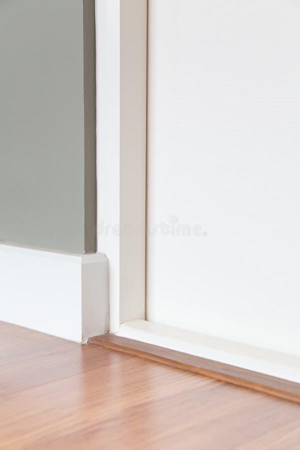 Pokoju kąt, biały drzwi, drewniana podłoga, siwieje ścianę zdjęcie royalty free