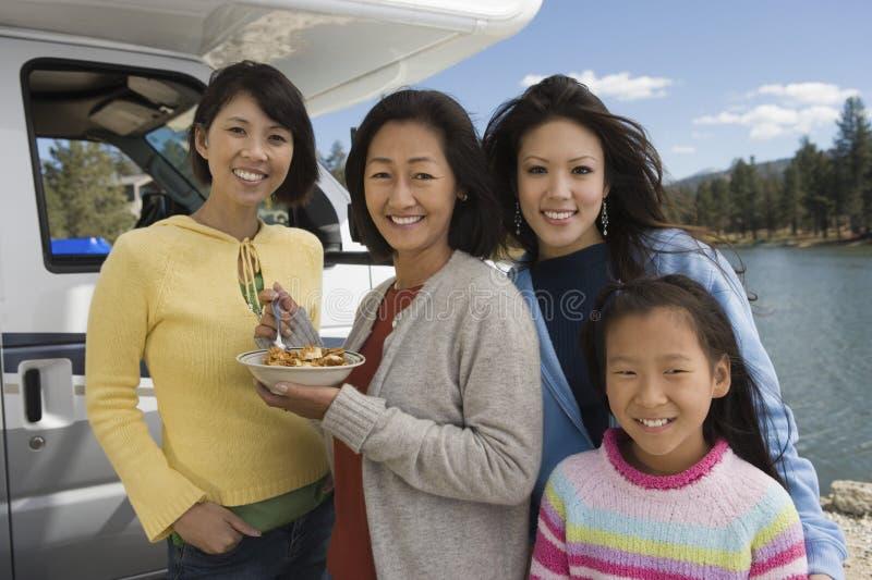 Pokolenie kobiety je śniadaniowego outside RV przy jeziorem zdjęcie royalty free