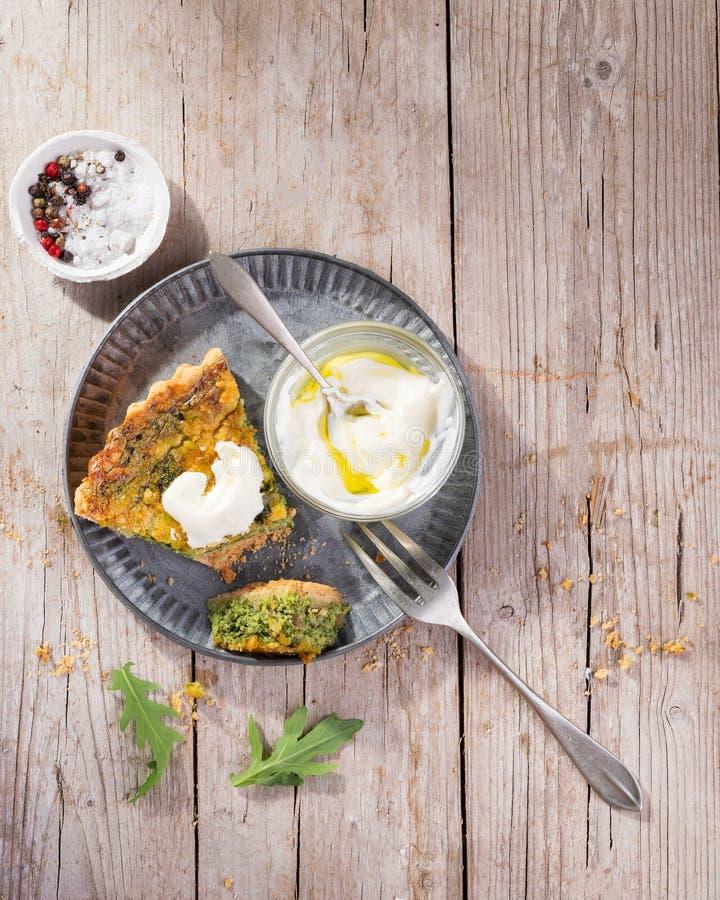 Pokrajać Quiche na talerzu z arugula, cebulą, szpinakami, mozzarellą, feta i kumberlandem na nieociosanym tle, odgórny widok, prz zdjęcie stock