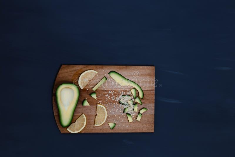Pokrojeni avocado i cytryny kliny na drewnianej desce zdjęcie royalty free