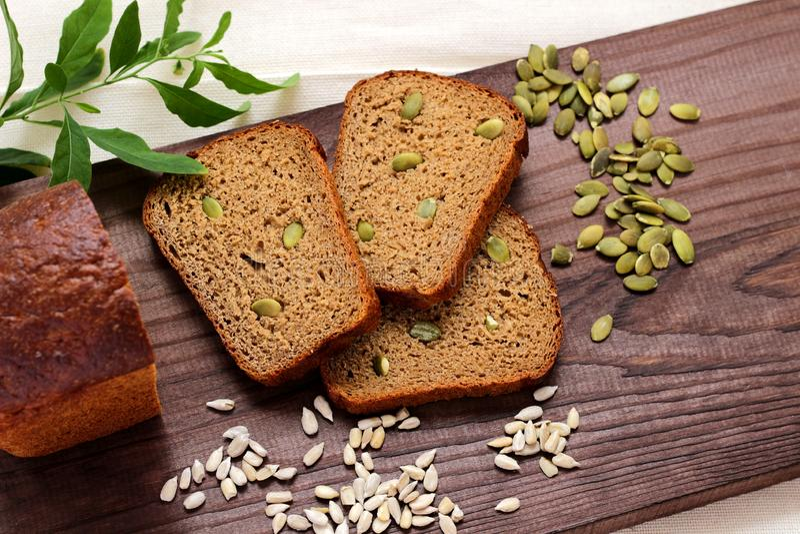 Pokrojeni kawałki i loa żyto chleb kłamają na drewnianej tnącej desce obraz stock