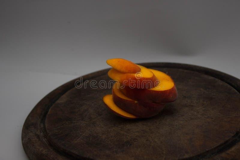 Pokrojona brzoskwinia na przecinanie stole zdjęcia stock