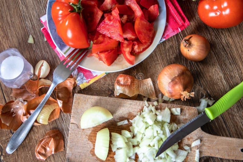 Pokrojona cebula na kuchni desce, ca?a cebula i pomidory w tle, obrazy stock
