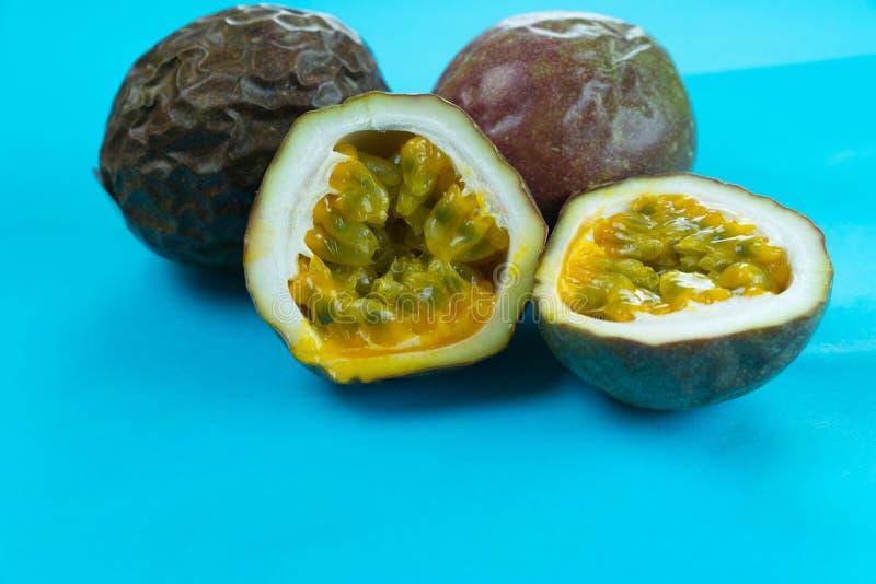 Pokrojona i cała purpurowa pasyjna owoc na jaskrawym turkusowym tle fotografia stock