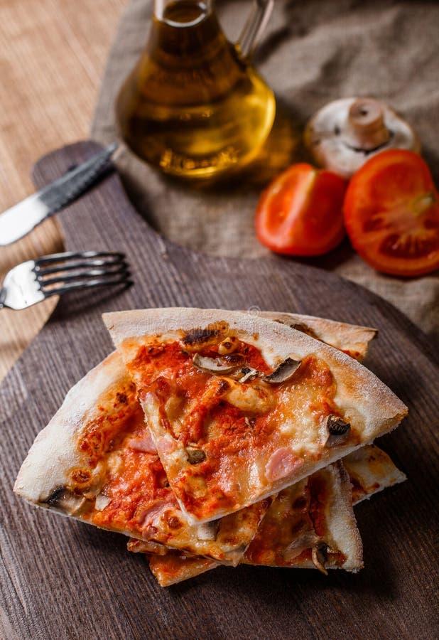 Pokrojona pizza z baleronem, serem, pieczarkami i pomidorowym kumberlandem na drewnianej tnącej desce, obraz royalty free