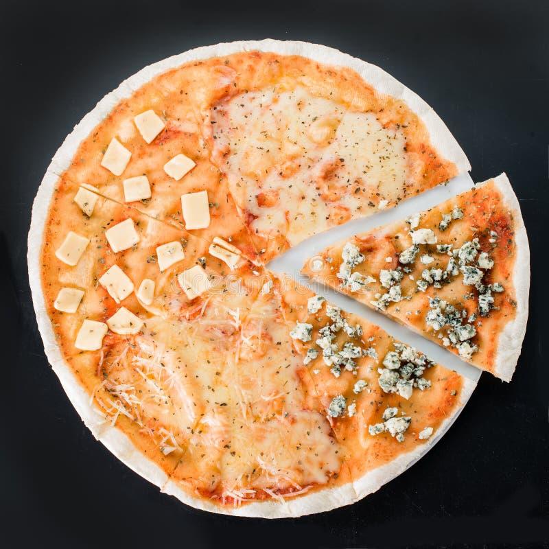 Pokrojona pizza z różnymi rodzajami ser na ciemnym tle zdjęcia stock