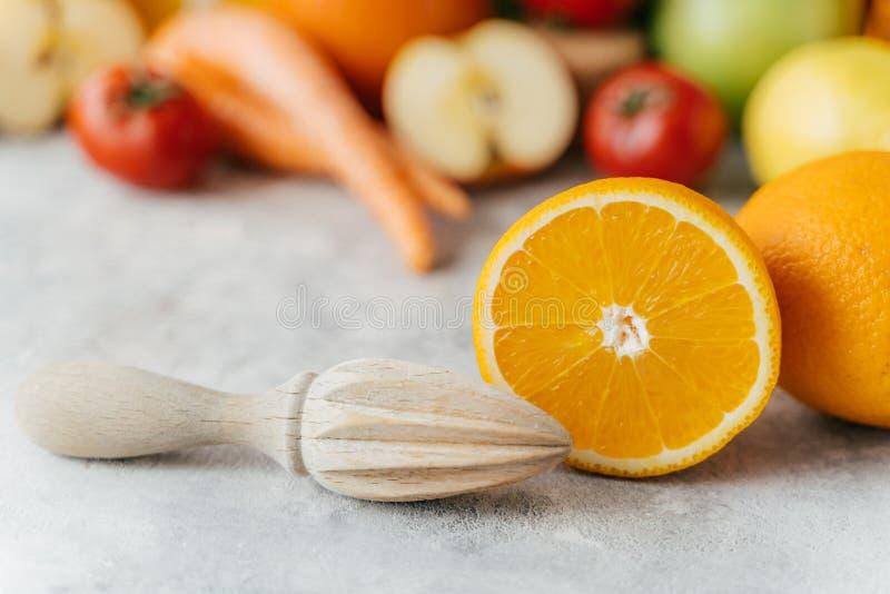 Pokrojona pomarańcze i drewniany wyciskacz przeciw zamazanemu owoc i warzywo tłu Gnieść świeża cytrus owoc Zdrowy obraz stock