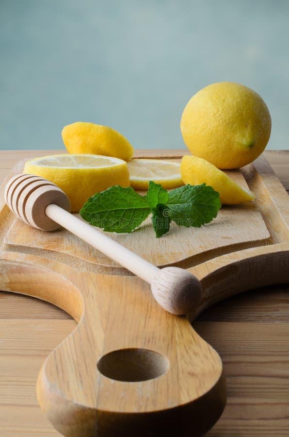 Pokrojone cytryny i miętówka liście na Drewnianej ciapanie desce obraz stock