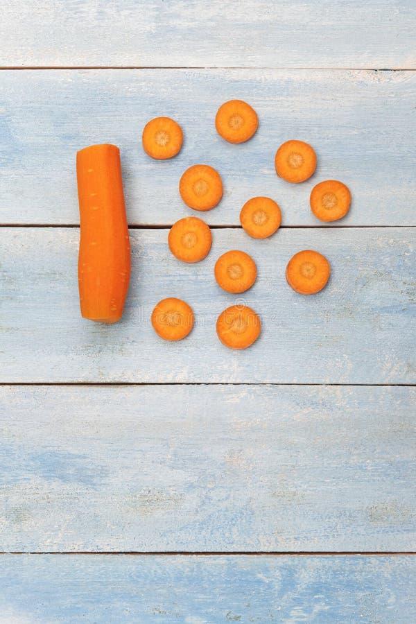 Pokrojone marchewki na błękitnej drewnianej desce obrazy stock