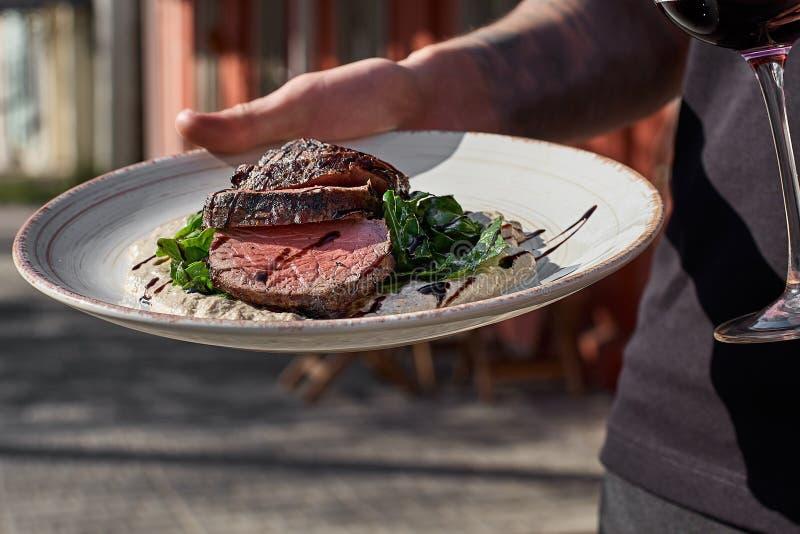 Pokrojony średni rzadki piec na grillu wołowina stek z pieczarkowym kumberlandem i zieleniami talerz w rękach kelner fotografia royalty free