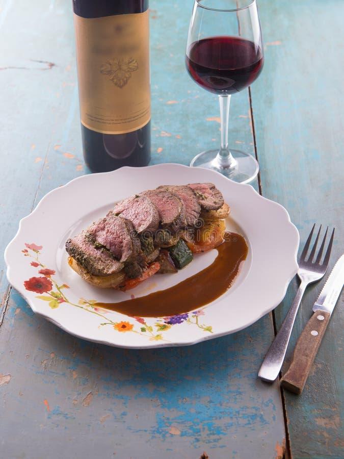 Pokrojony średni rzadki stek słuzyć z piec na grillu czerwonym winem i warzywami obraz royalty free