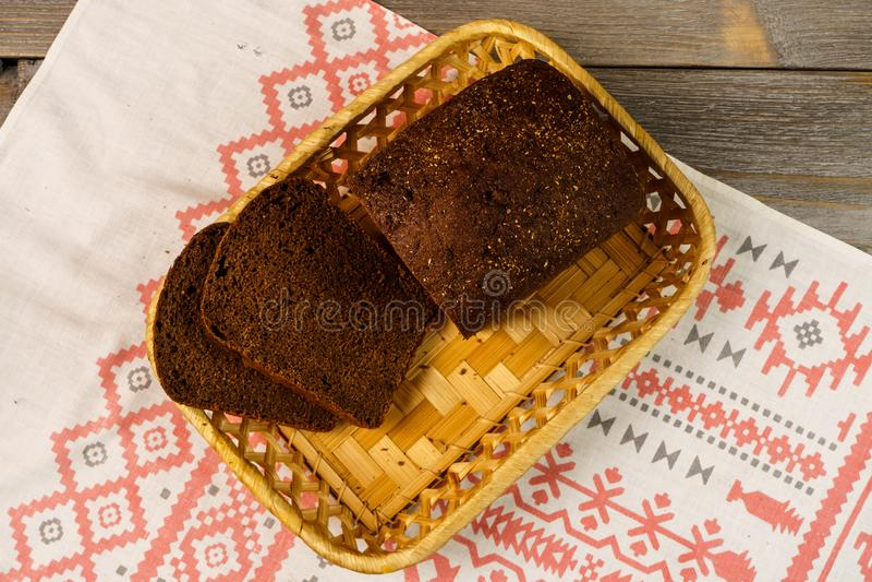 Pokrojony żyto chleb w koszykowej pozyci na ręczniku Bochenek świeży żyto chleb z plasterkami na drewnianym wieśniaka stole obrazy royalty free