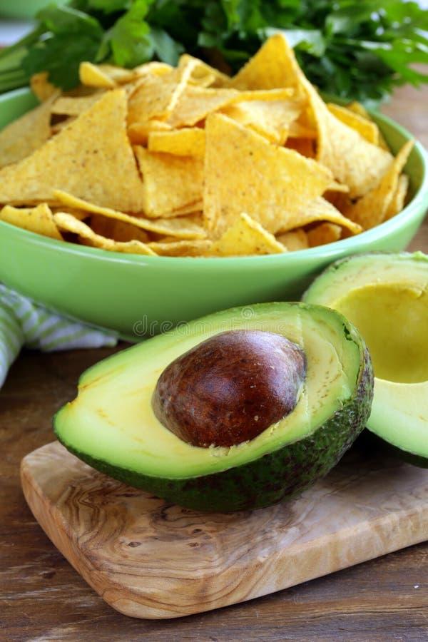 Pokrojony avocado na drewnianej desce tortilla kukurydzanych układach scalonych i obraz royalty free