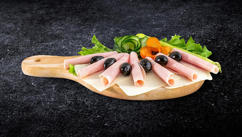 Pokrojony baleronu salami dekorował na drewnianej desce z oliwkami, pomidor zdjęcia stock