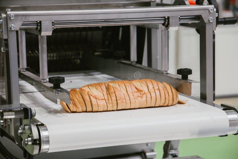Pokrojony biały chleb w tnącej maszynie, wypiekowego wyposażenia selekcyjna ostrość zdjęcie stock