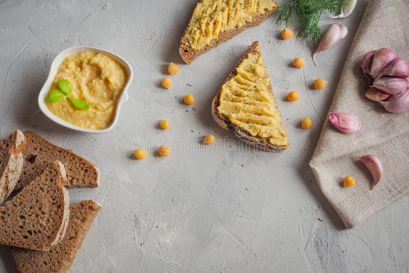 Pokrojony całej banatki chleb z hummus, chickpea i czosnkiem na popielatym betonowym tle, obraz royalty free