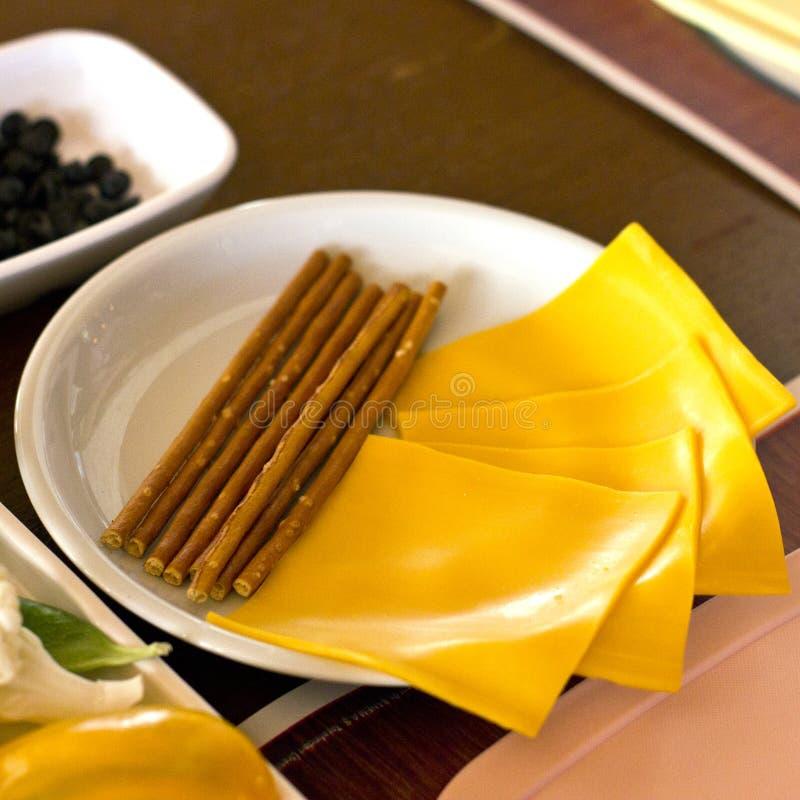 Pokrojony cheddaru ser i solący kije na białym talerzu obrazy royalty free