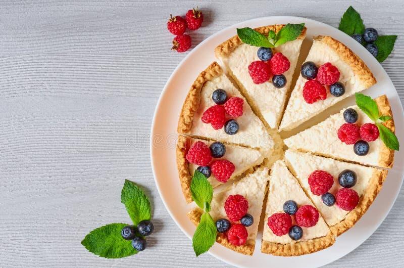 Pokrojony cheesecake z świeżymi jagodami na białym talerzu - zdrowy organicznie deser Klasyczny Nowy Jork cheesecake obraz royalty free