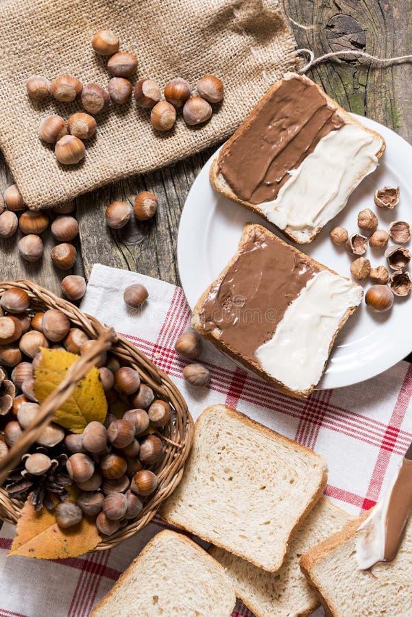 Pokrojony chleb w talerzu z czekoladową śmietanką i dokrętkami fotografia stock