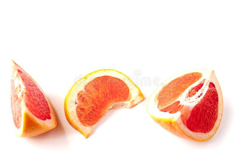Pokrojony czerwony grapefruitowy odosobniony na bia?ym t?a ci?ciu w trzy kawa?ka obraz royalty free