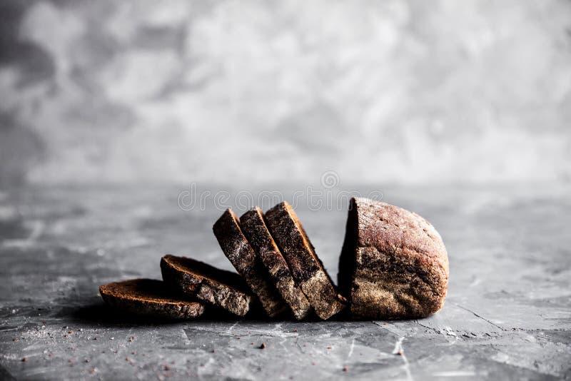 Pokrojony domowej roboty bia?y pszeniczny chleb z pszeniczn? m?k? na starej czarnej piekarnik tacy jako t?o Odg?rny widok fotografia royalty free