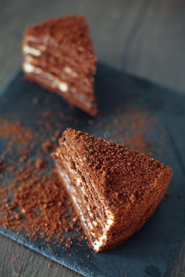 Pokrojony Domowej roboty Miodowy czekoladowy tort z dojną śmietanką na czerń łupku desce Odgórny widok dwa kawałki fotografia royalty free