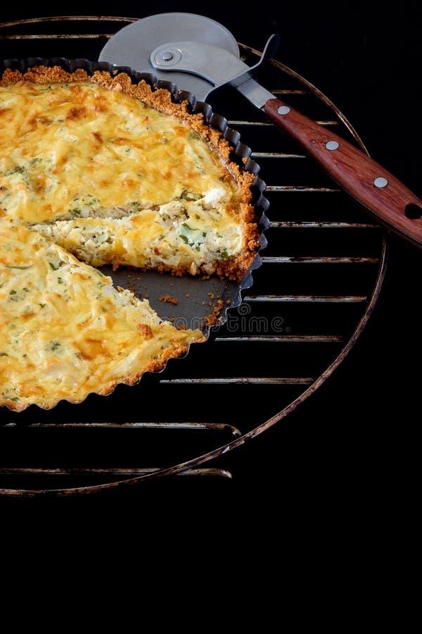 Pokrojony domowej roboty quiche z kurczakiem, cebula, pietruszka i pizza nóż na czarnym tle, serową i zieloną fotografia stock