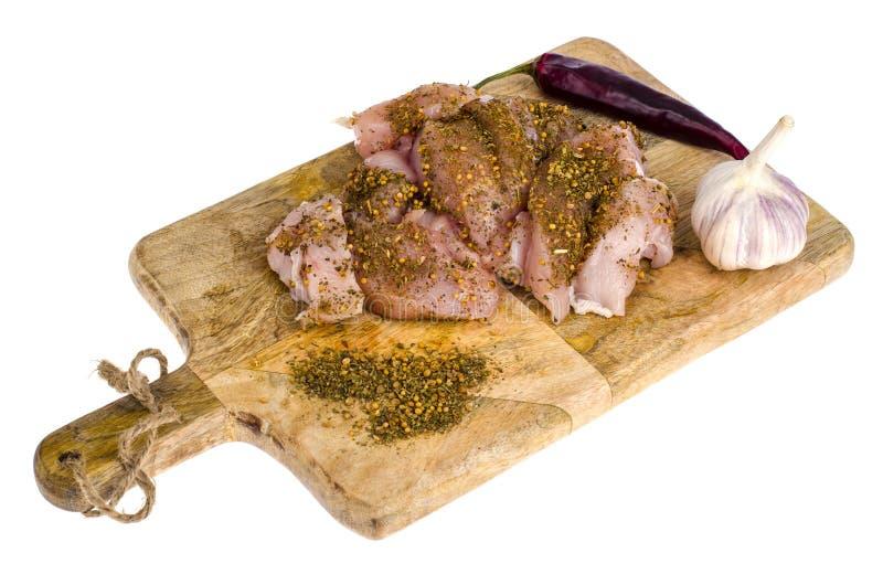 Pokrojony kurczak polędwicowy z pikantność na drewnianej kuchennej tnącej desce obraz stock