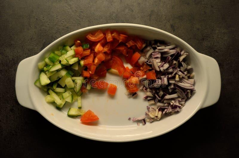 Pokrojony ogórek, pomidor i czerwona cebula w białym pucharze na kuchennym stole, zdjęcie royalty free