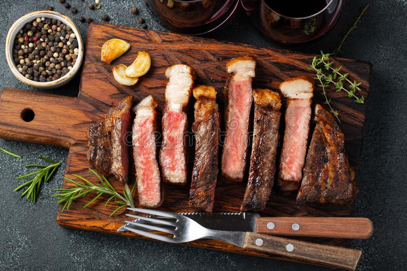 Pokrojony stek Striploin, piec na grillu z pieprzem, czosnek, sól i macierzanka, słuzyć na drewnianej ciapanie desce z szkłem cze fotografia royalty free