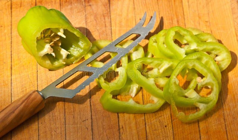 Pokrojony zielony pieprz i serrated rzemieślnika nóż obraz royalty free