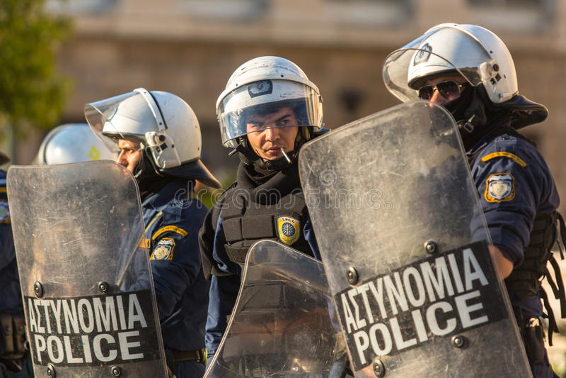 Polícia de motim com seu protetor, tampa da tomada durante uma reunião na frente da universidade de Atenas imagens de stock royalty free