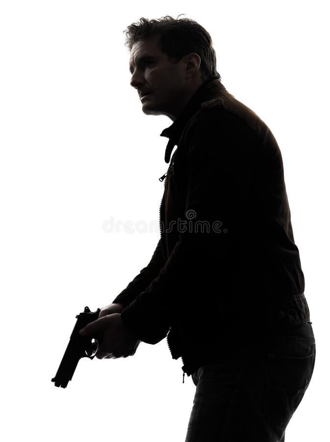 Polícia do assassino do homem que guarda a silhueta da arma foto de stock