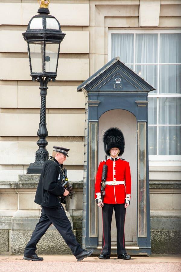 Polícia e protetor real no Buckingham Palace, Londres, Grâ Bretanha, Reino Unido fotografia de stock