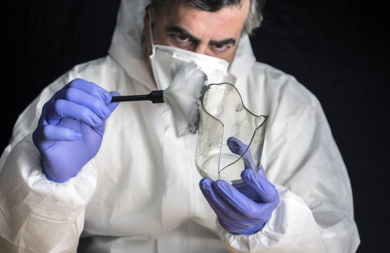 A polícia perita obtém impressões digitais de uma garrafa de vidro quebrada no laboratório criminoso foto de stock