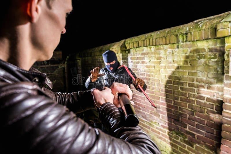 Polícia que aponta a tocha e a pistola para o cracksma assustado rebentado fotografia de stock royalty free