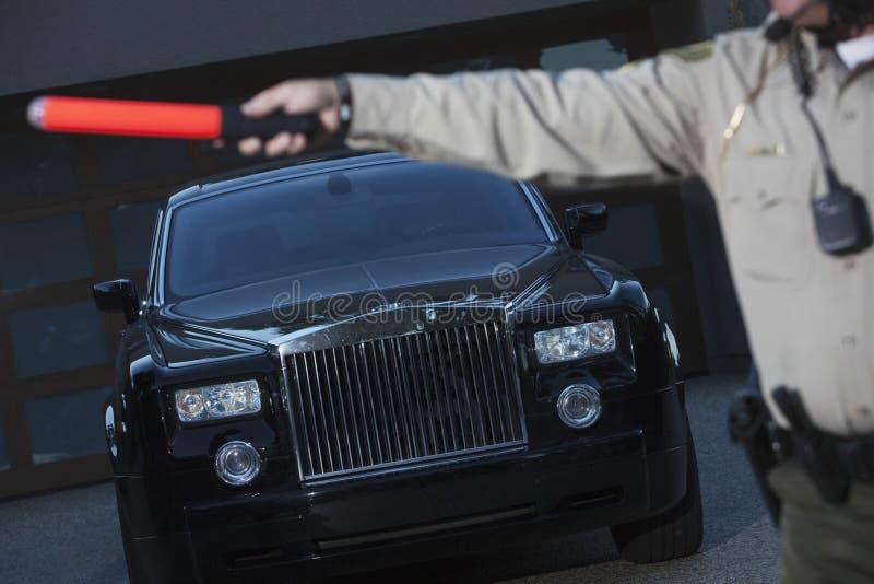 Polícia que guarda o bastão da mão para parar o carro imagem de stock