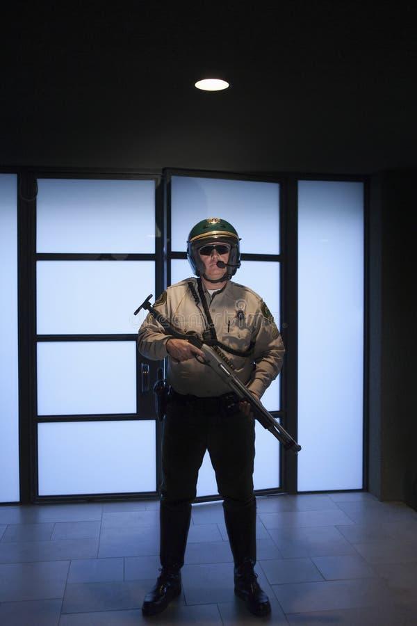 Polícia que mantém o rifle contra a porta fotografia de stock royalty free