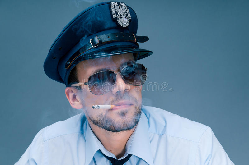 Polícia viciado aos cigarros fotografia de stock