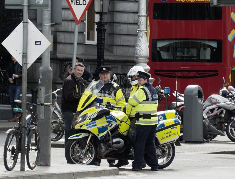 Polícias irlandeses que compartilham de um gracejo com um transeunte em uma rua movimentada em Dublin imagem de stock