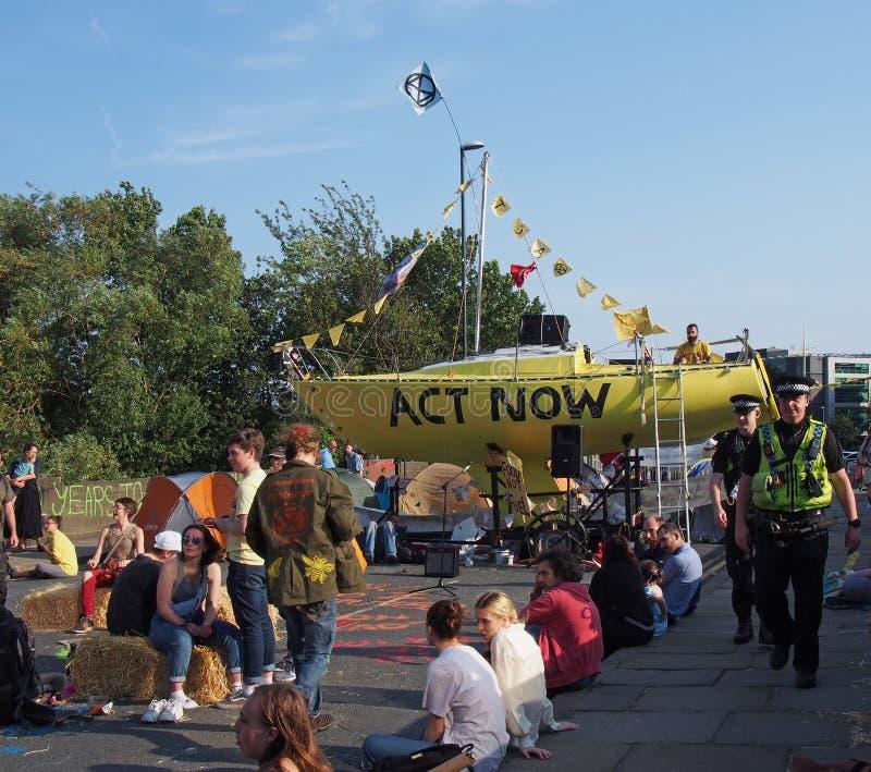 Polícias que andam em torno do assento dos povos e o barco e as barracas que obstruem o lugar do bridgewater da estrada em leeds  foto de stock royalty free