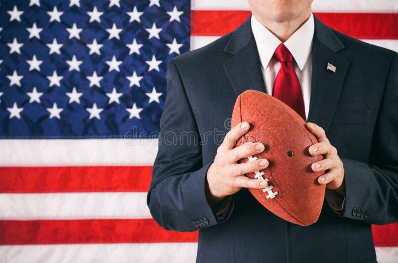 Político: Homem que guarda o futebol americano imagens de stock