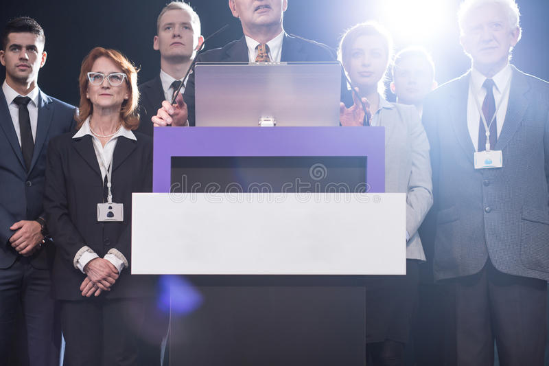 Políticos que rodean la plataforma en medios conferencia imagen de archivo libre de regalías