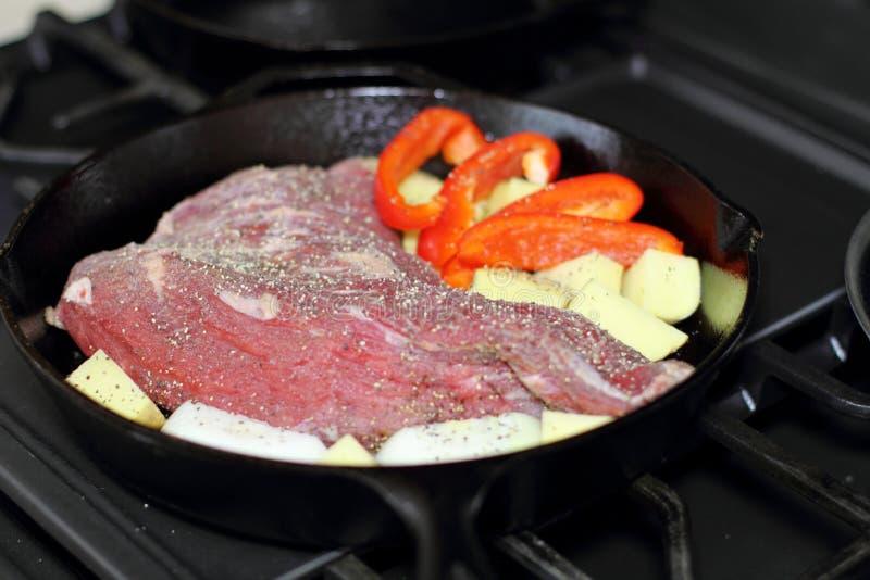 Pol?dwicy tritip stek w lanej ?elaznej niecce z grulami i cebulami fotografia royalty free