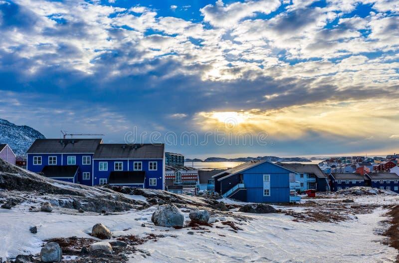 Polaire zonsondergang over Inuit-huizen op de rotsachtige heuvels met sneeuw, Nuu royalty-vrije stock afbeelding